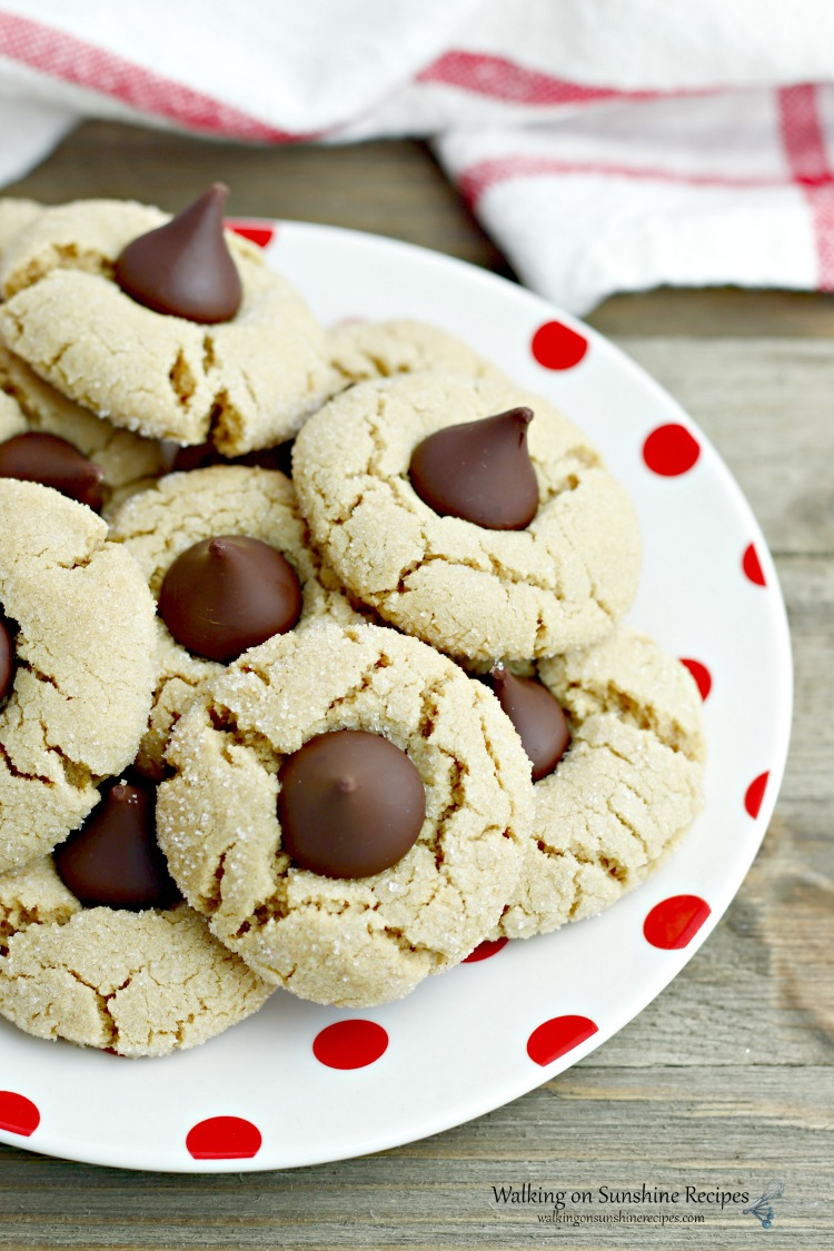 Peanut Butter Blossoms on white plate with red dots and kitchen towel in background.