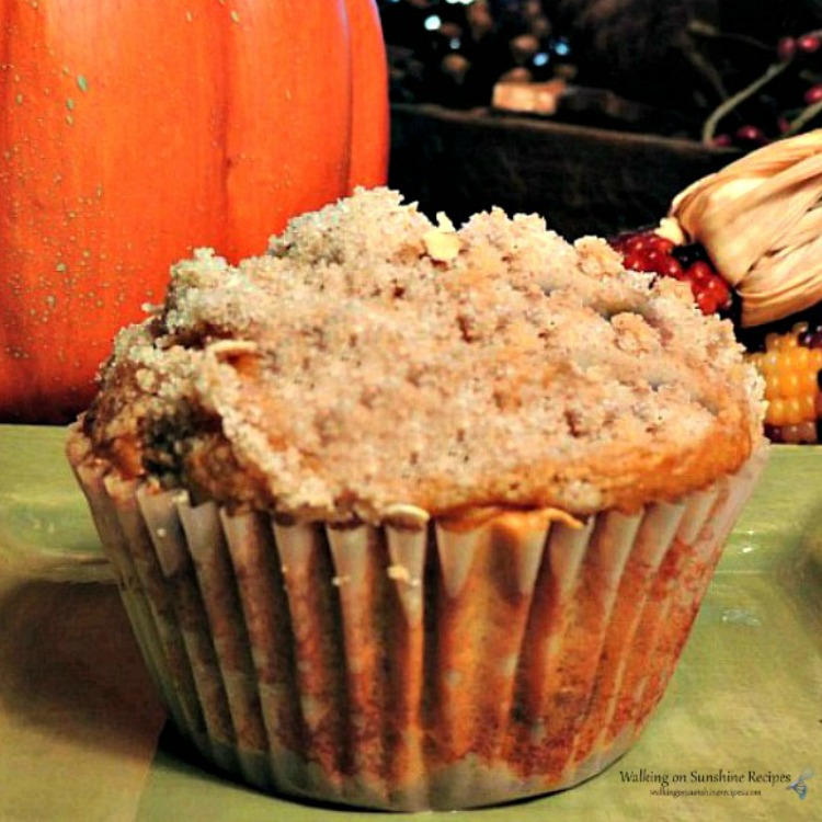 pumpkin muffin with crumb topping on green plate.