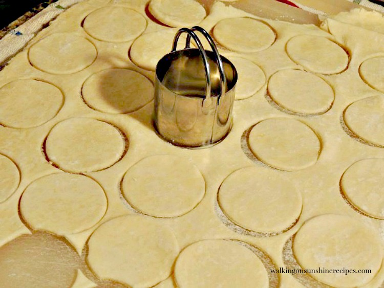 Mini quiche pie crust dough being cut out with small biscuit cutter from Walking on Sunshine