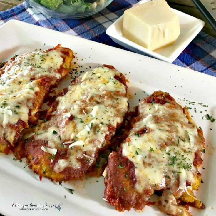 Chicken Parmesan Baked on white platter with cheese and salad on side
