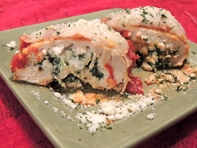 Chicken Stuffed with Ricotta Cheese and Spinach on green plate closeup.