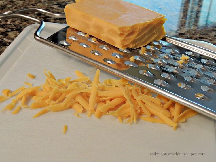 block of cheddar cheese being grated on cutting board.