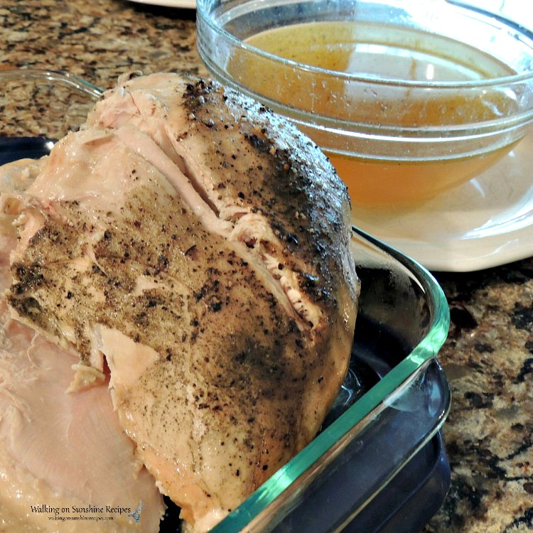 Turkey breast in glass baking dish with bowl of chicken broth.