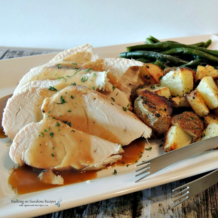 Crock Pot Turkey Breast on white platter with roasted potatoes and green beans.