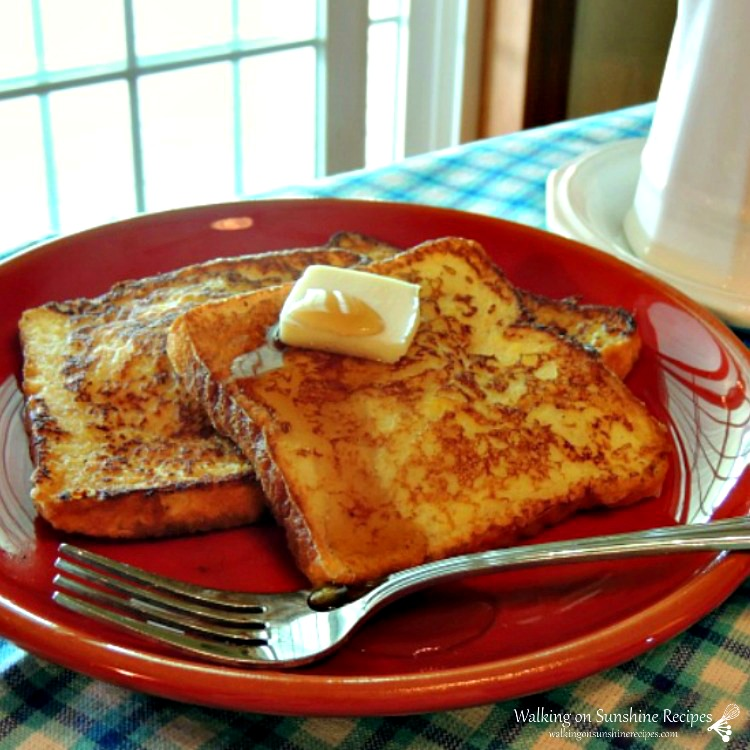 Classic French Toast served on a red plate with butter and maple syrup.
