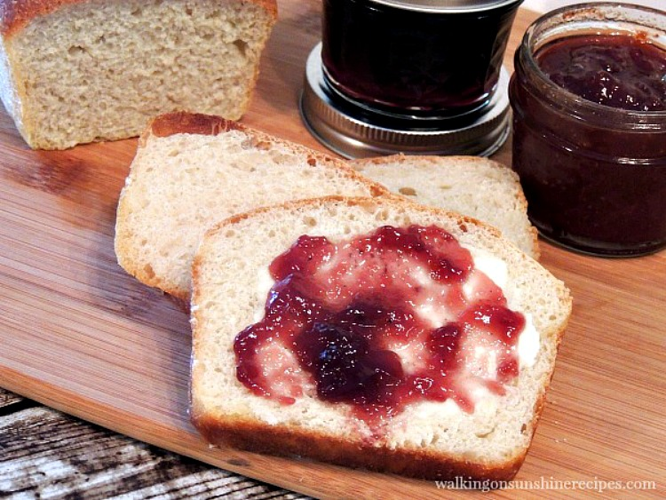 Homemade White Bread on cutting board with jam and butter.