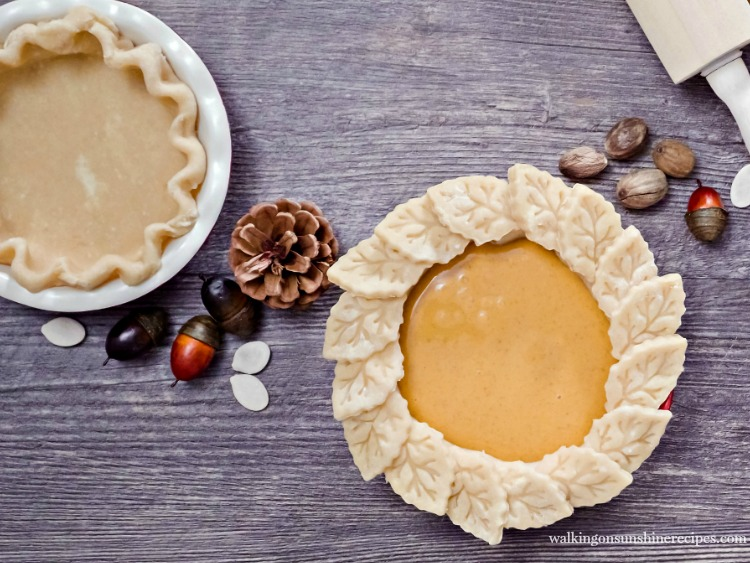 Decorating pie crust with leaf cut outs.