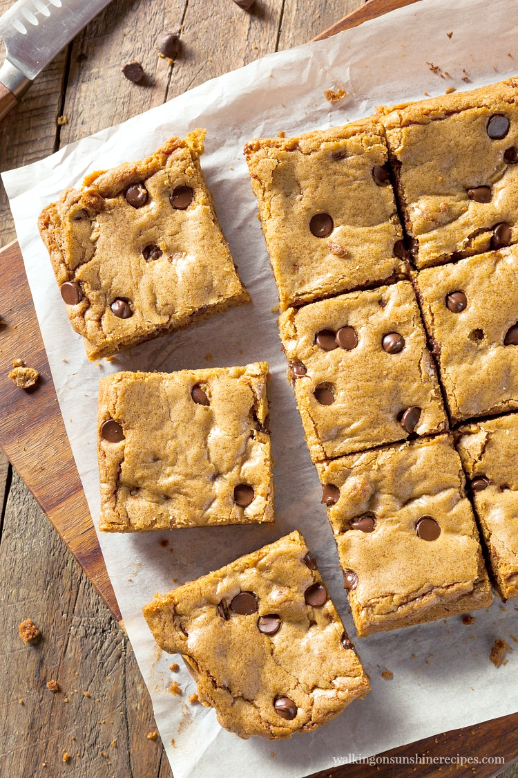 Chocolate Chip Cookie Bars on parchment paper sliced with knife on cutting board.