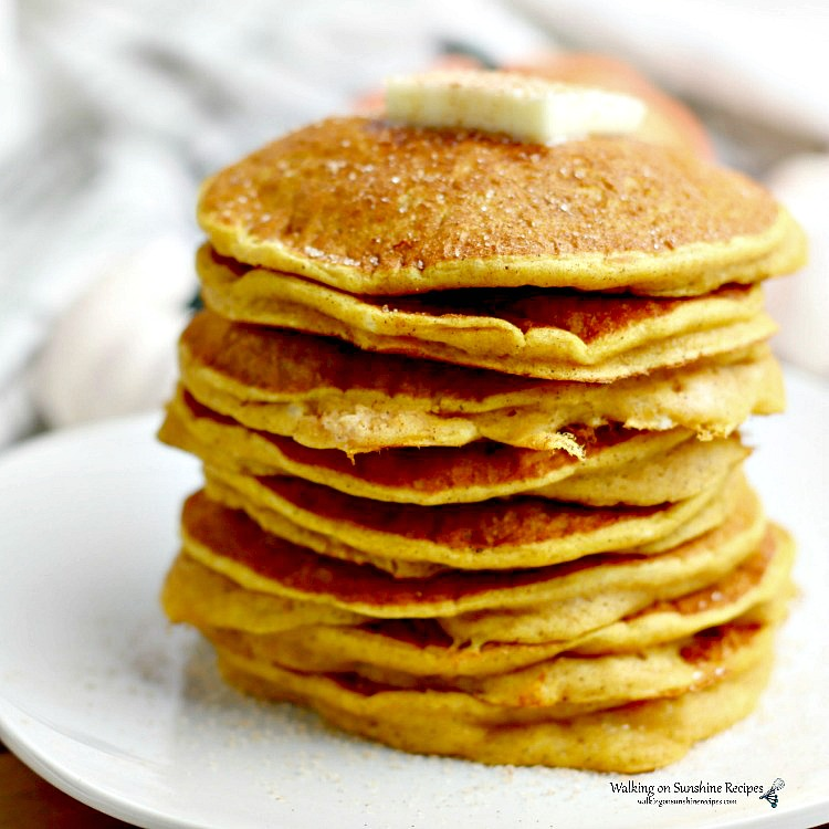 Pancake Mix Pumpkin Pancakes stacked on a white plate with butter and cinnamon sugar sprinkled on top.