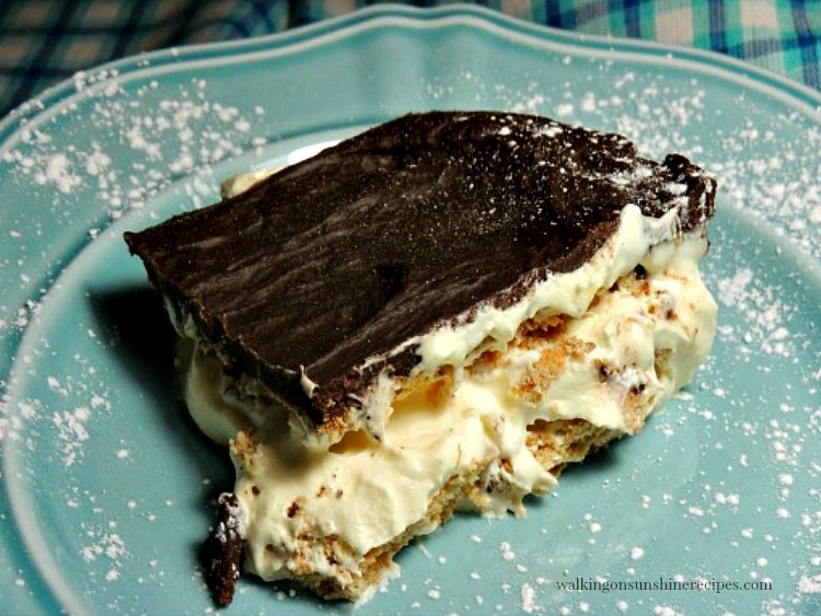 Chocolate Eclair Pudding Cake on blue plate sprinkled with powdered sugar.