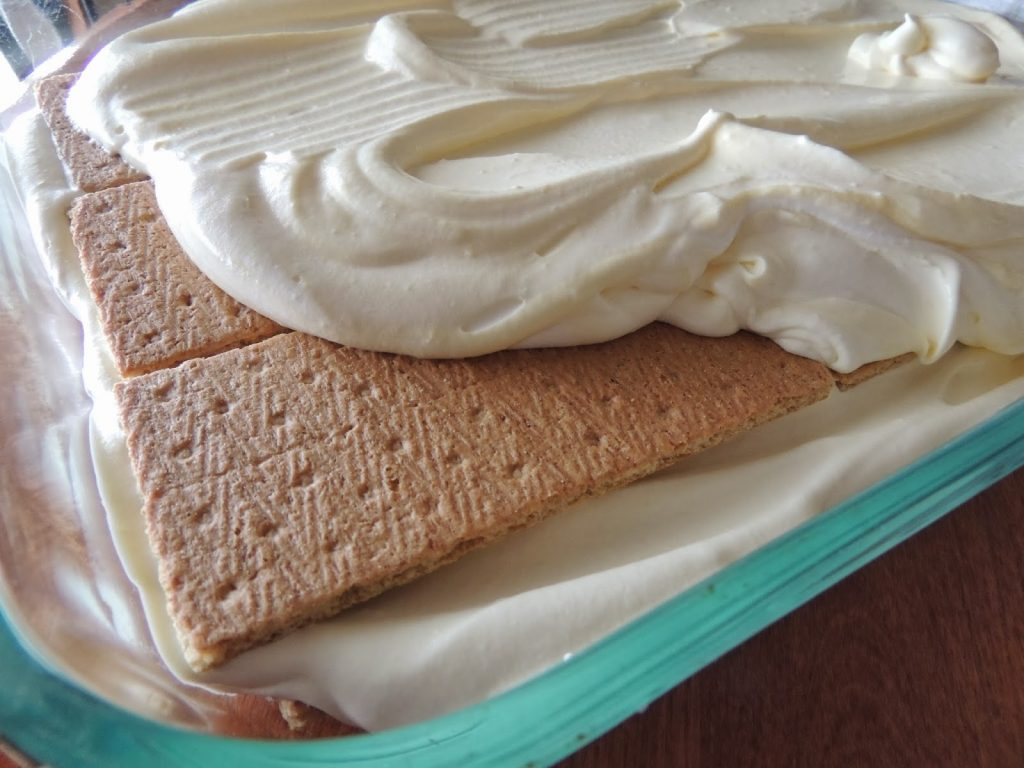 Layers of graham crackers and pudding mix for Chocolate Eclair Pudding Pie from Walking on Sunshine Recipes.