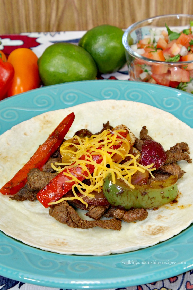 Easy Steak Fajitas on top of Flour Tortillas with Cooked Peppers and Onions and limes.