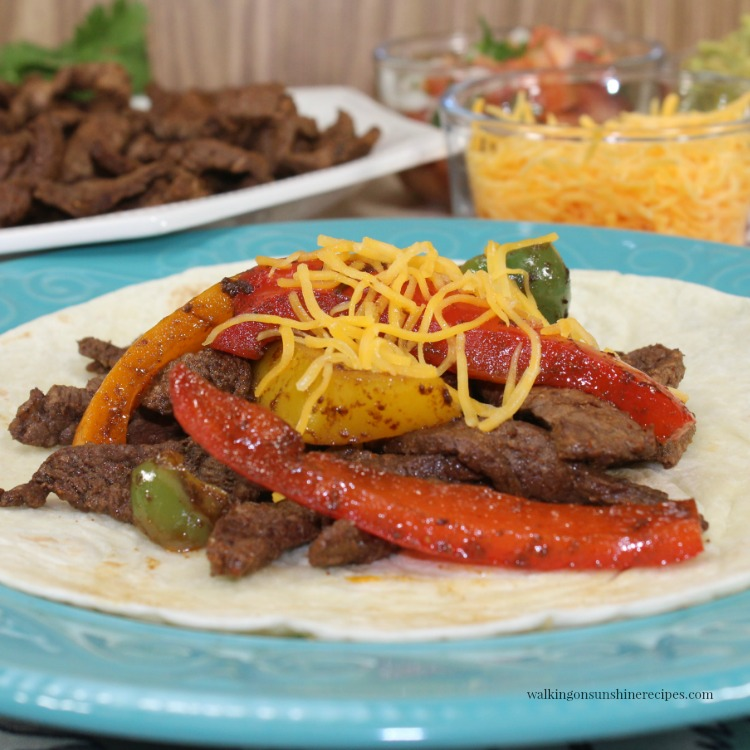 Easy Steak Fajitas on flour tortilla which cheese on top of blue plate.