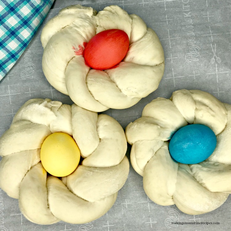 Three Italian Easter Bread rings with colored eggs.