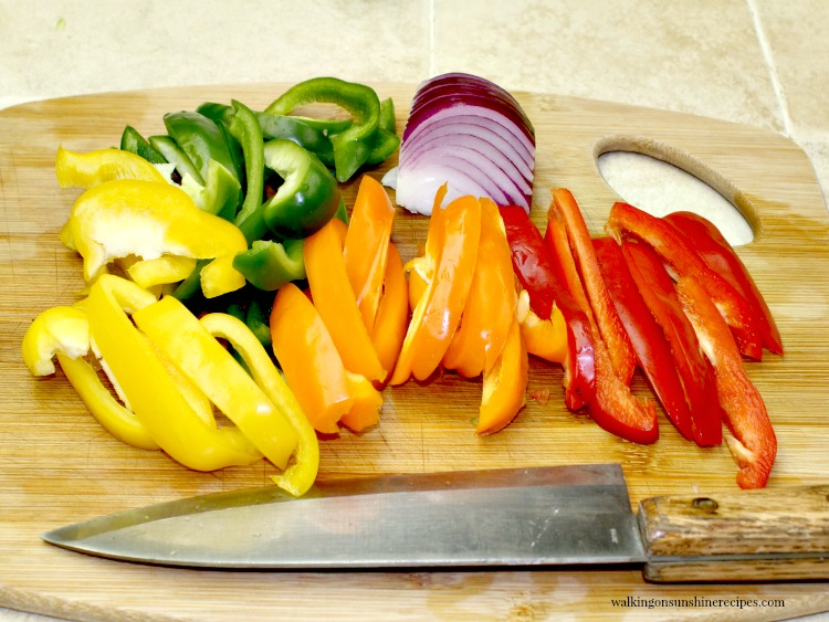 Yellow, Red, Green and Orange Peppers sliced on cutting board for Easy Steak Fajitas