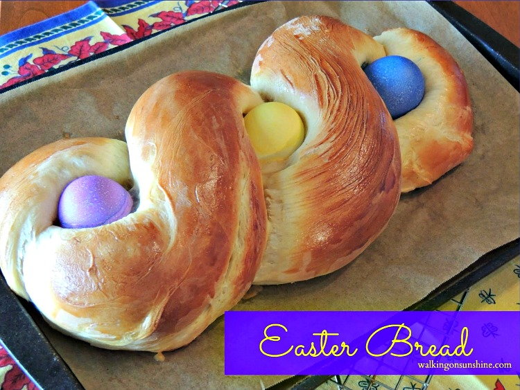 Italian Easter Bread with colored eggs on parchment paper baking tray.