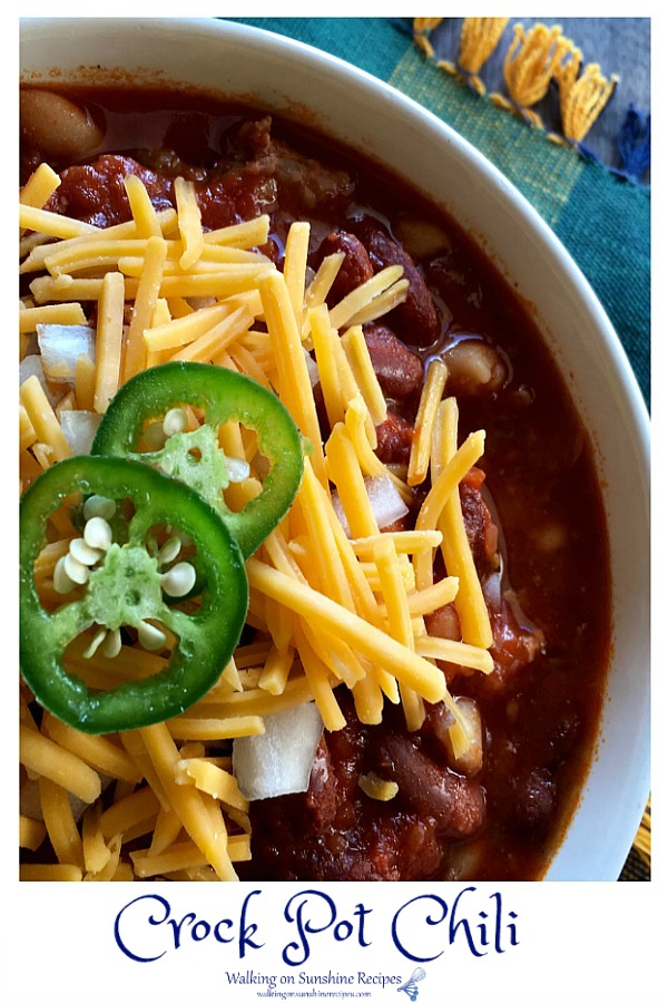 Closeup of ground beef chili with red kidney beans in white bowl with cheddar cheese and jalapenos.