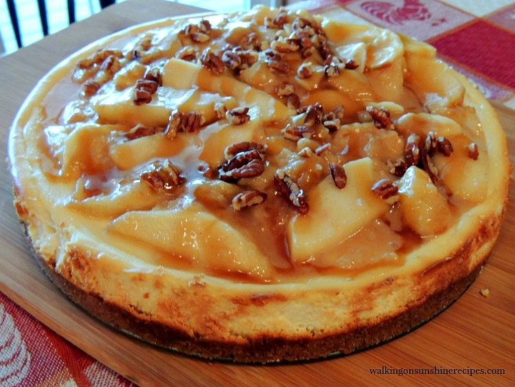 Cheesecake with Caramel Apple Topping on cutting board.