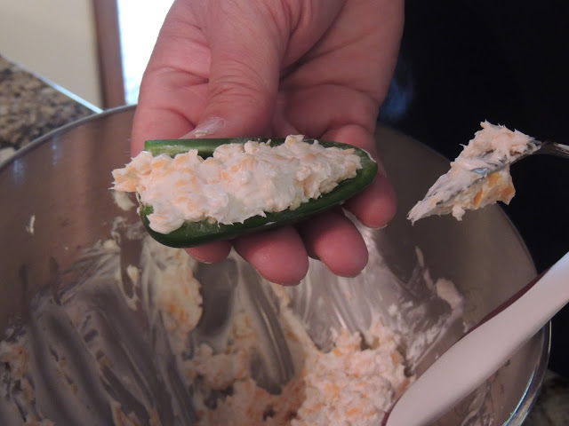 Using a small spoon, stuff the jalapeno peppers with the cream cheese mixture.