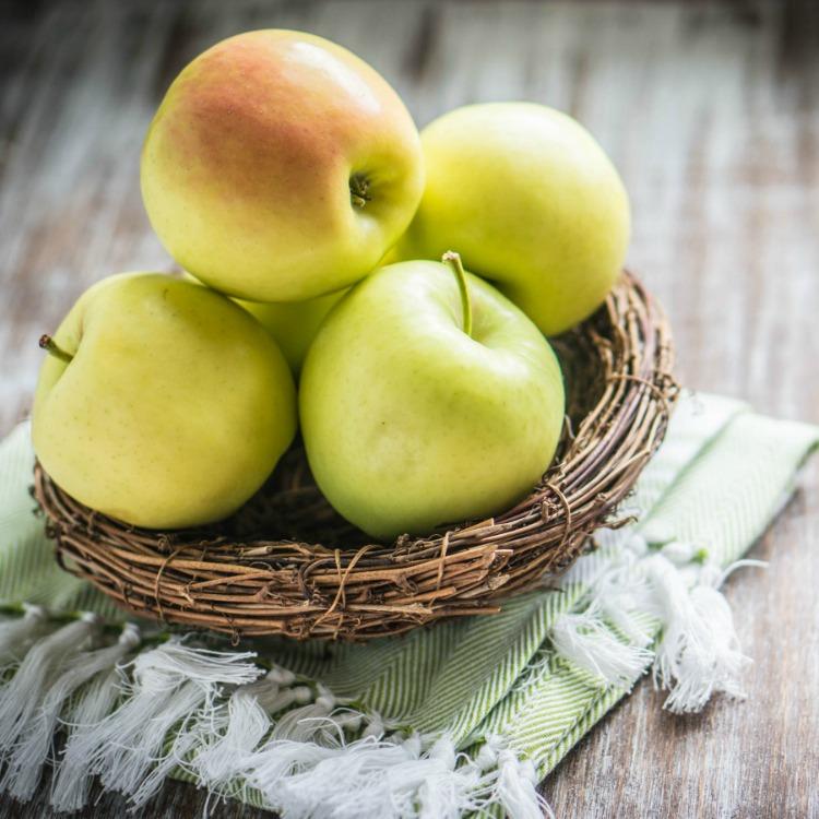 Green apples in twine basket.