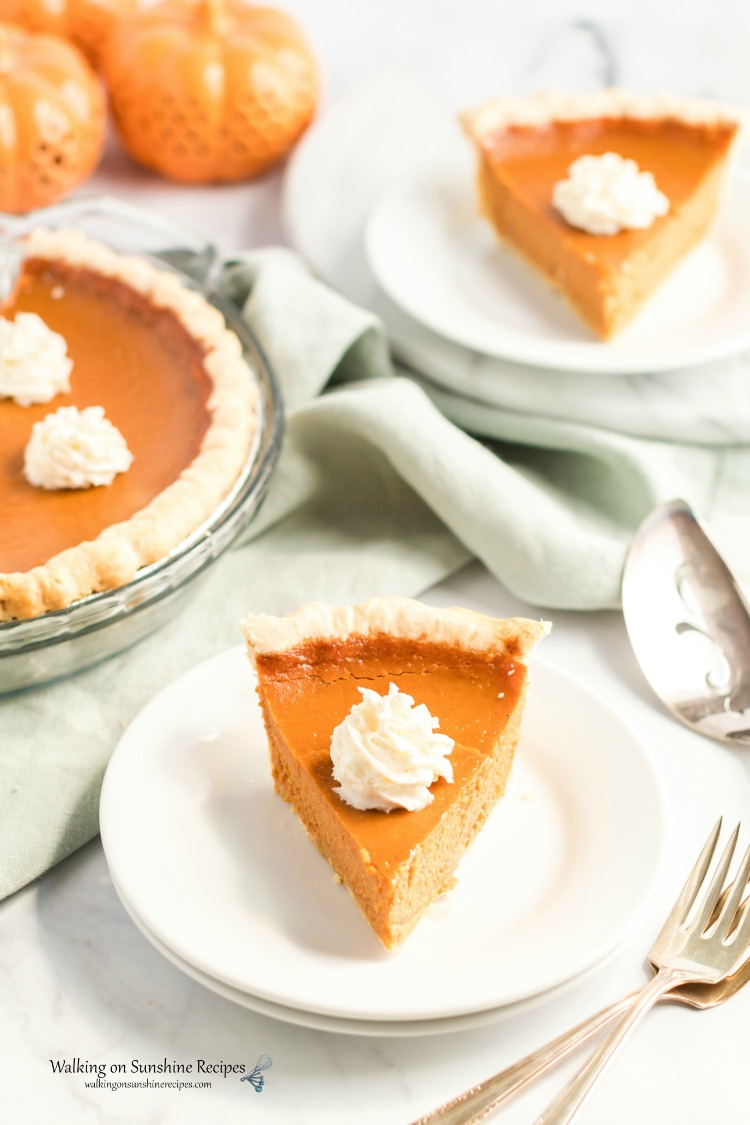 Pumpkin pie on plate slice with whipped cream.