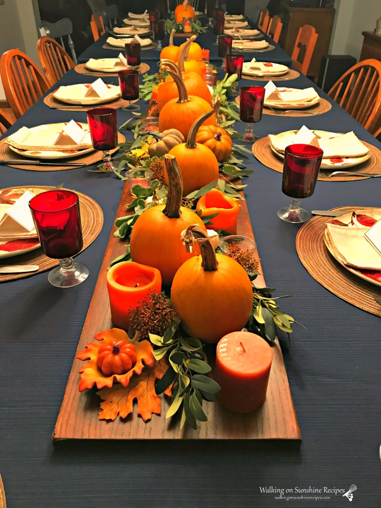 Thanksgiving table set with pumpkins, greenery and candles.
