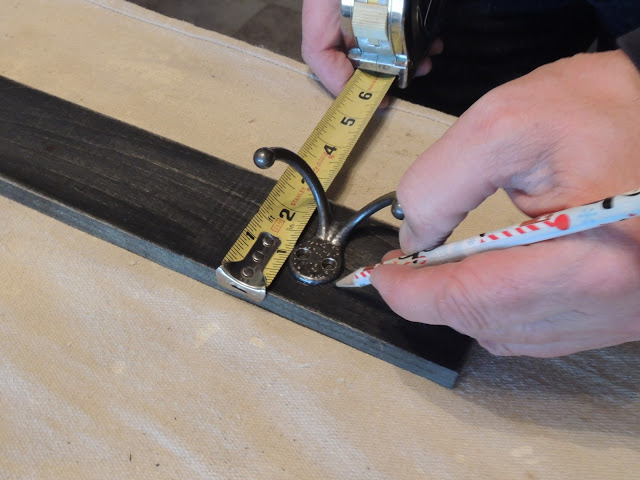 Measuring where to put the hooks for the DIY Industrial Style Message Center from Walking on Sunshine.