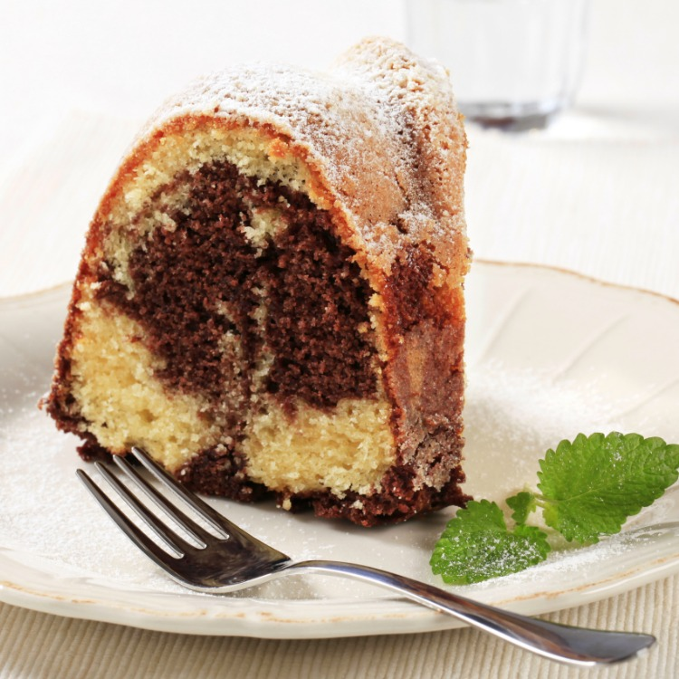 Closeup piece of Marble Bundt Cake on white plate with a sprig of mint from WOS