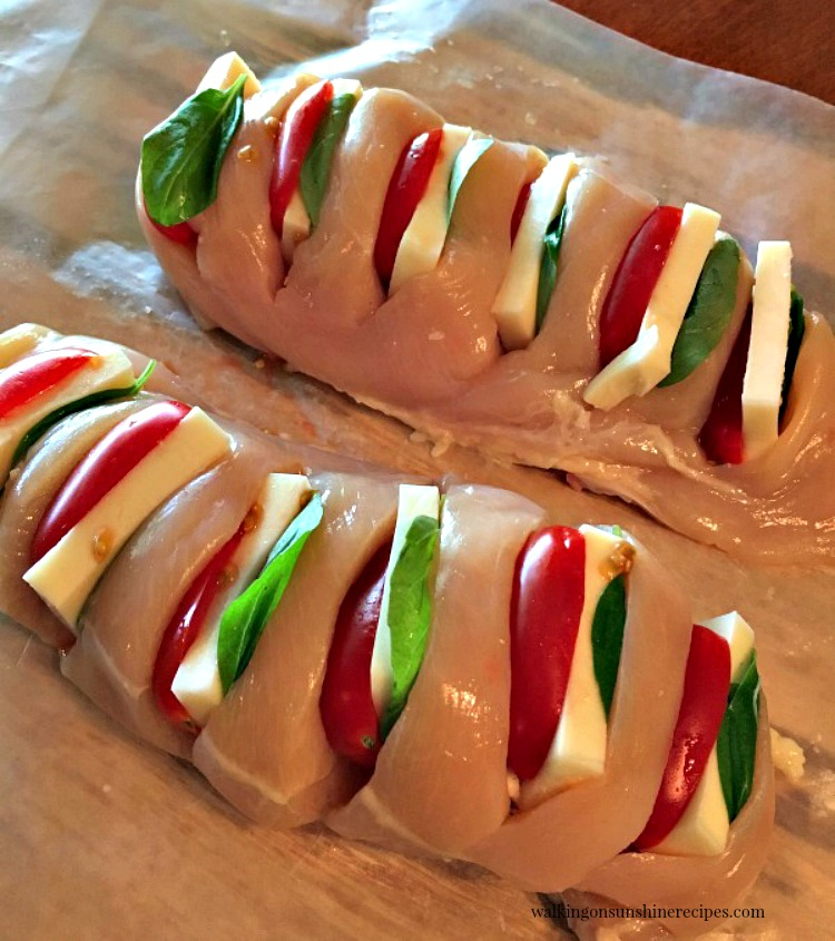 Chicken Stuffed with Mozzarella, Tomato and Basil on cutting board with waxed paper from Walking on Sunshine Recipes