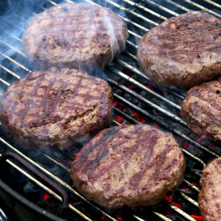 Hamburgers on grill with smoke
