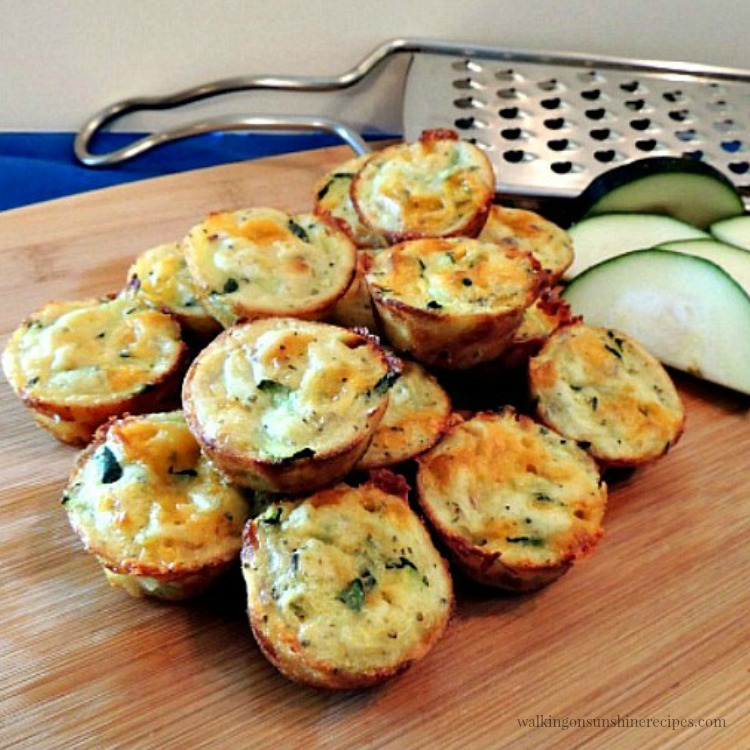 Zucchini Puffs on wooden board with cheese grater.