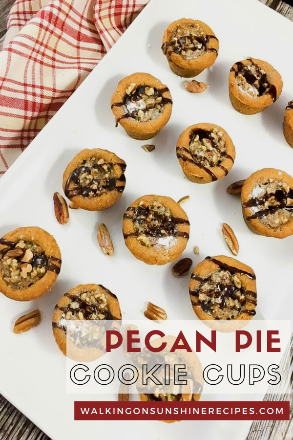 Pecan Pie Cookie Cups on white tray drizzled with chocolate syrup.