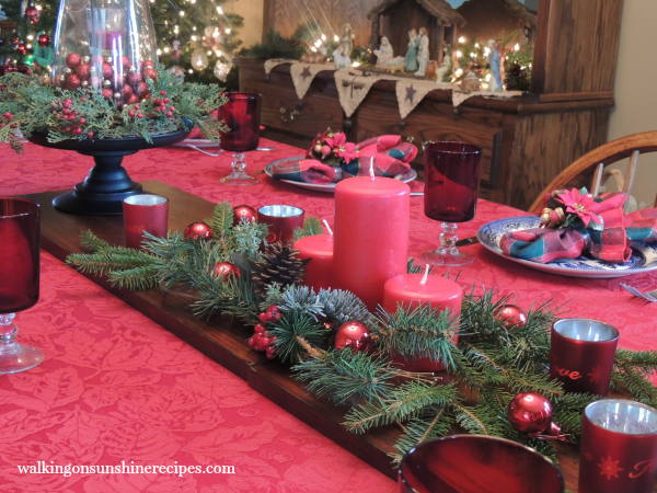 Closeup of the table setting looking into the dining room with the nativity scene and Christmas tree.
