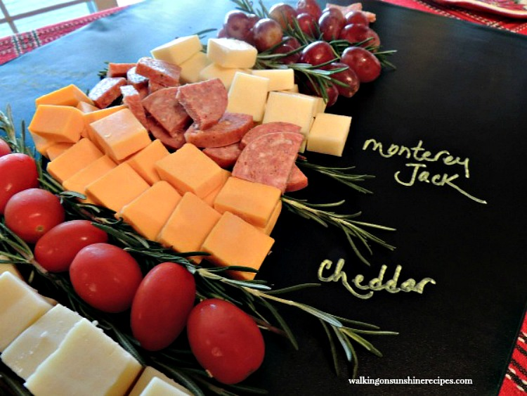 Cheese, tomatoes, salami and grapes on cheese board