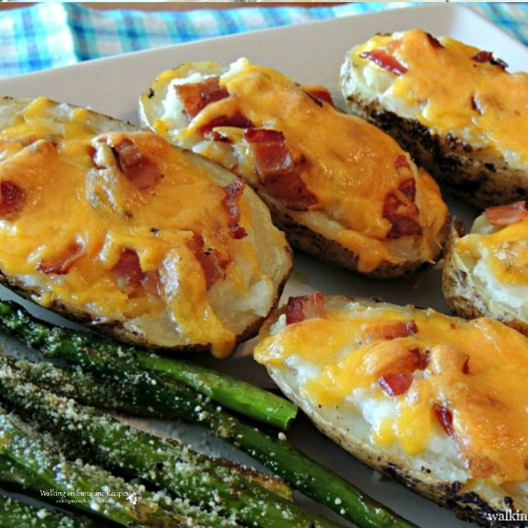 Twice baked stuffed potatoes on white tray with asparagus.