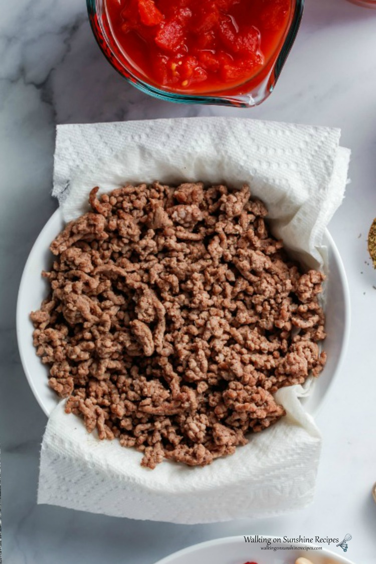 Browned Ground Beef draining in colander with paper towels.