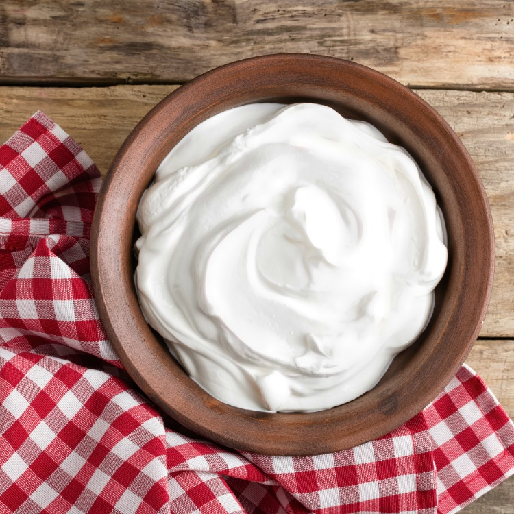 Homemade Whipped Cream in wooden bowl on wooden table top with red gingham napkin.