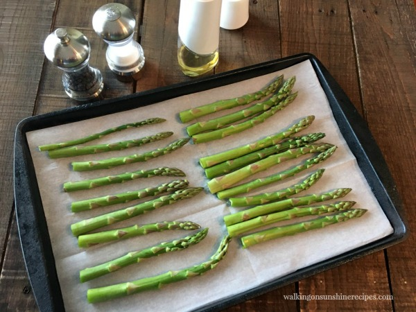 Lay asparagus flat on a baking tray lined with parchment paper from Walking on Sunshine
