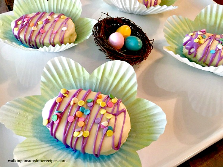Mini Easter Egg Cakes closeup on white platter in flower shaped cupcake liners from Walking on Sunshine Recipe