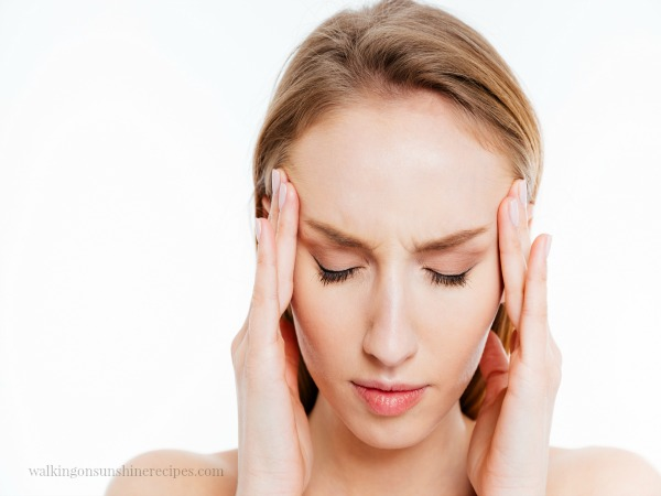 Woman with hands on forehead and terrible headache.