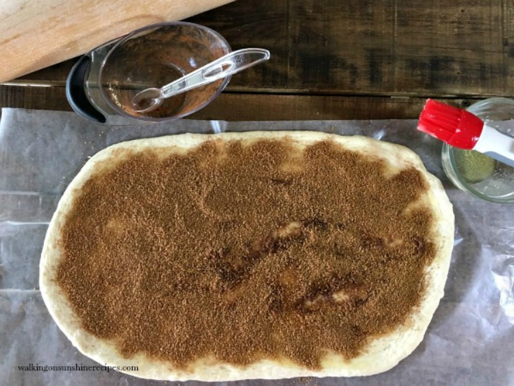 Spread brown sugar cinnamon mixture over dough for cinnamon rolls from Walking on Sunshine