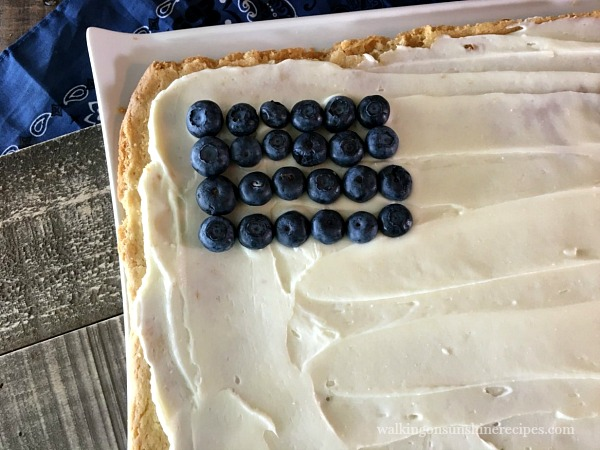 Add the blueberries for the stars for the Flag Fruit Sugar Cookie Pizza