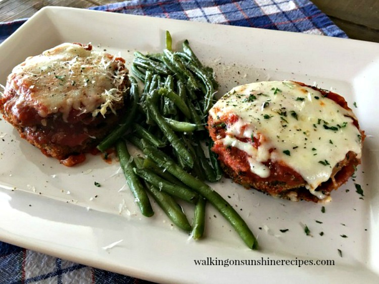 Baked Eggplant Parmesan stacks on white tray with green beans.