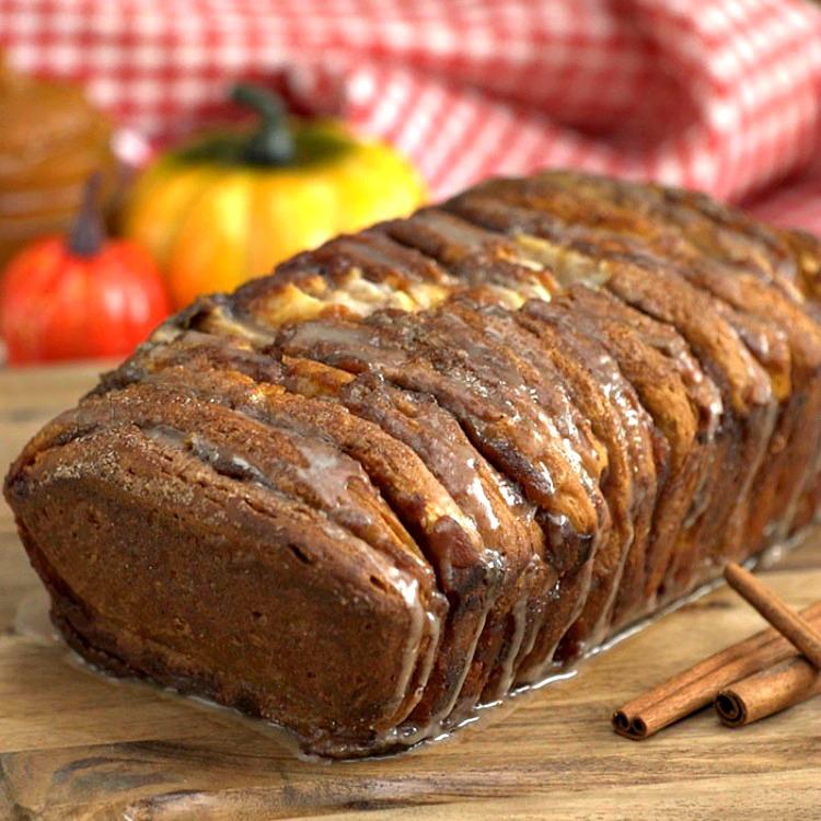 Pumpkin Spice Pull Apart Bread with cinnamon sticks on cutting board
