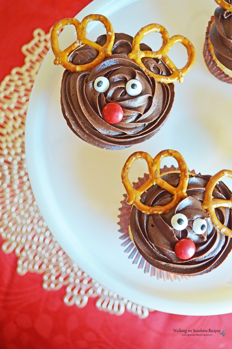 Reindeer Cupcakes on White Cake plate with pretzel twists and candy pieces.
