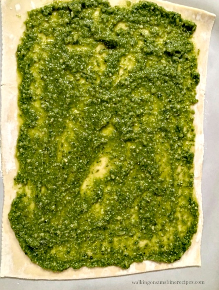 Spread the pesto sauce on top of one sheet of puff pastry for Christmas Tree Puff Pastry Appetizer from Walking on Sunshine Reci