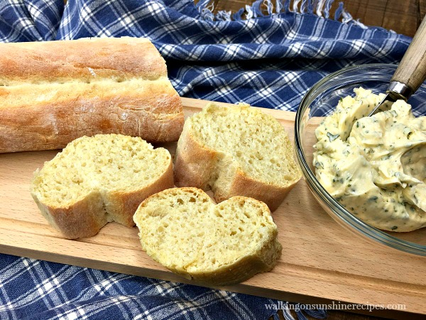 Homemade French Baguette sliced with homemade garlic butter on cutting board with blue checked napkin.