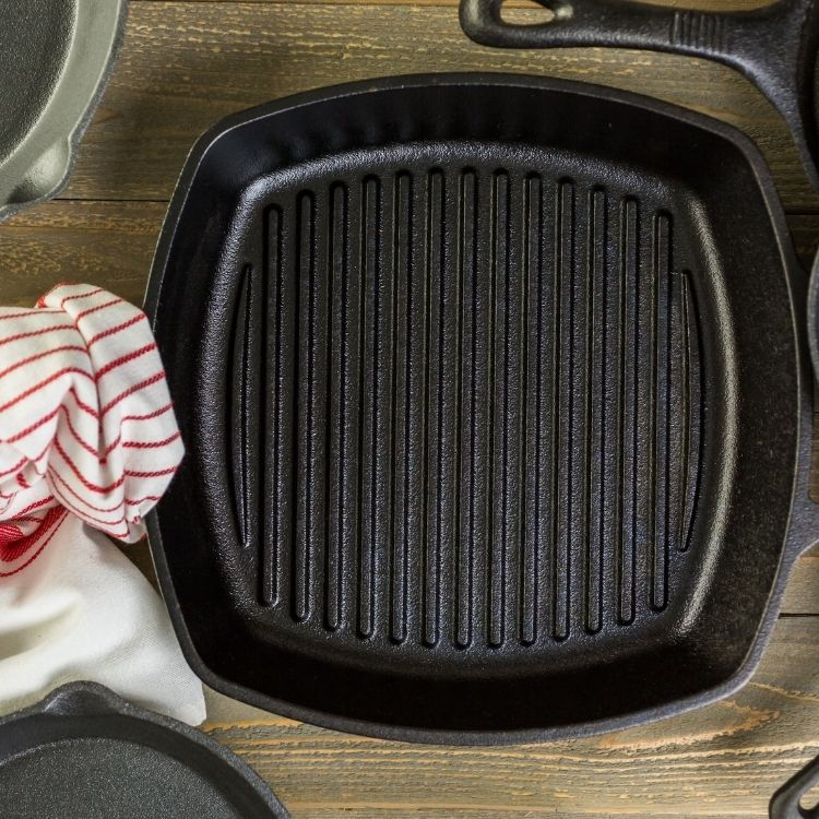 Cast iron grill pan on wooden board with dishtowel.