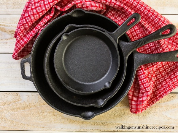 Stacked round cast iron pans on top of a red dish towel.