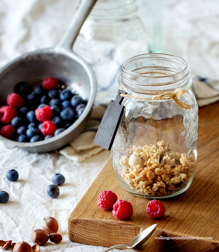 Add granola to mason jar for Fruit Yogurt Granola Breakfast Parfaits featured on Walking on Sunshine Recipes